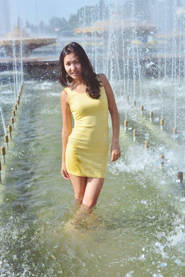 Mädchen in einem kurzen schleichenden Kleid mit dem langen nassen Haar und den Beinen in den Wassertröpfchen im Stadtbrunnen stockfoto