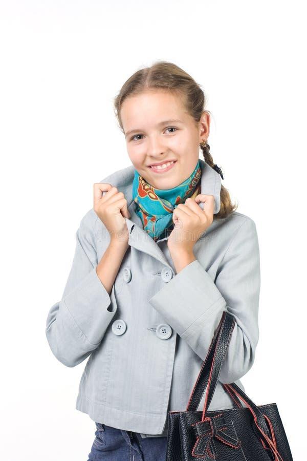 Mädchen in einem Mantel mit einem Beutel lizenzfreie stockfotografie