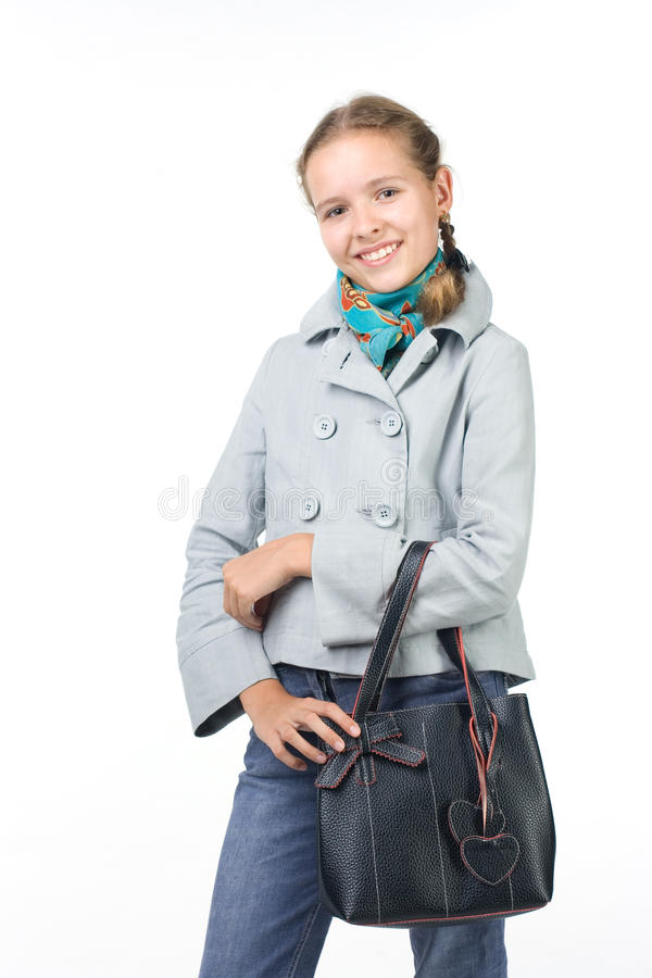 Mädchen in einem Mantel mit einem Beutel stockfotografie