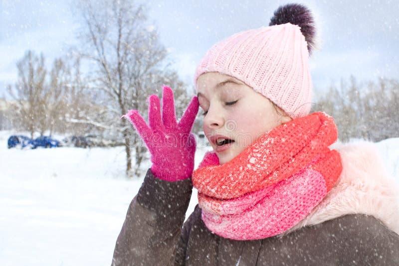 Mädchen in einem Mantel und in einer Strickmütze mit einem Bubo rüttelt weg den Schnee stockbild