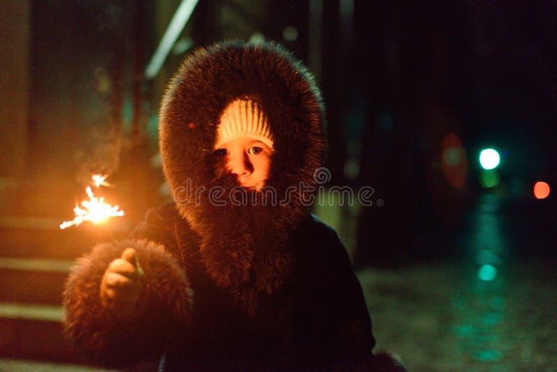 Mädchen in einem Pelzmantel mit einer Wunderkerze in der Hand stockfoto