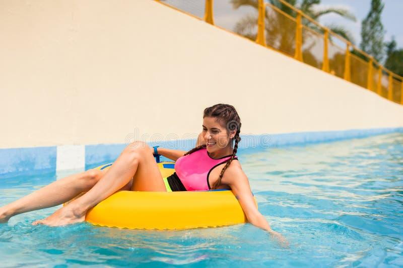 Mädchen in einem Pool, das in einem aufblasbaren Gummifloß sitzt lizenzfreie stockfotos