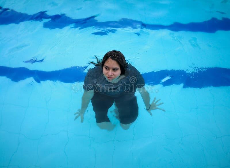 Mädchen in einem Pool mit schwarzer Kleidung an Blaues Wasser mit abstrakter Verzerrung lizenzfreie stockbilder