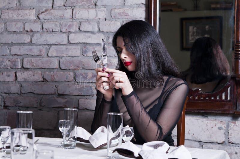 Mädchen an einem Restauranttisch lizenzfreie stockfotos