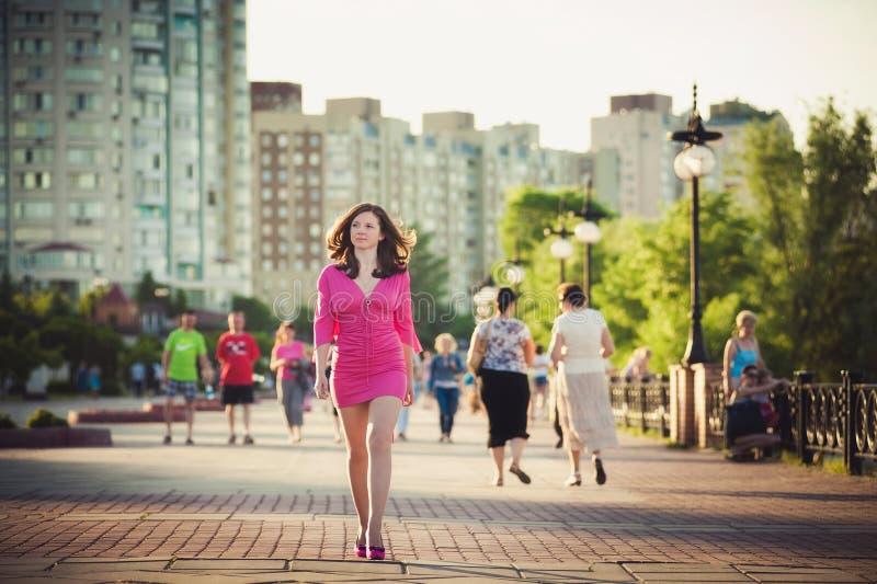 Mädchen in einem rosa Kleid geht um die Stadt lizenzfreie stockfotografie