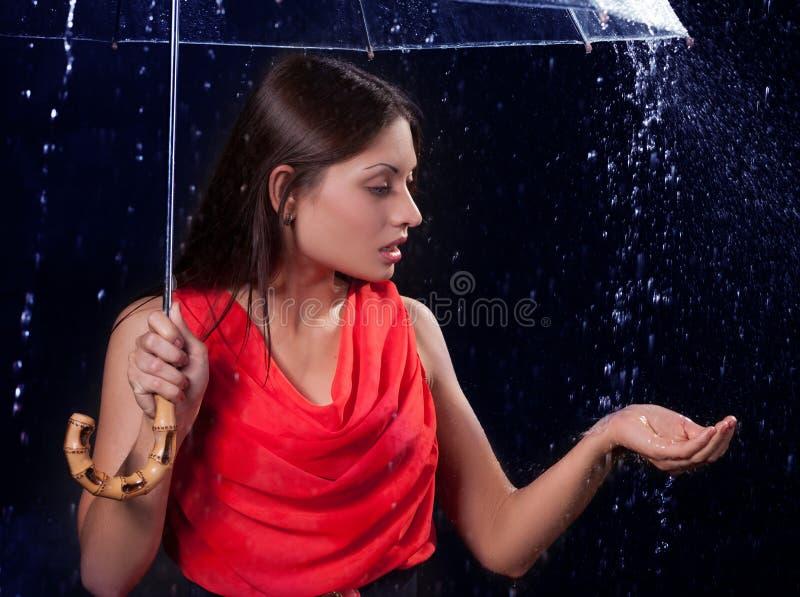 Mädchen in einem roten Kleid im Regen lizenzfreies stockbild