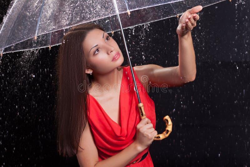 Mädchen in einem roten Kleid im Regen lizenzfreie stockfotografie