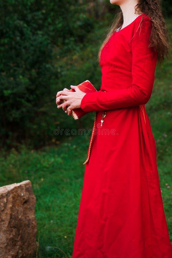 Mädchen in einem roten Kleid mit einem Buch stockfotos