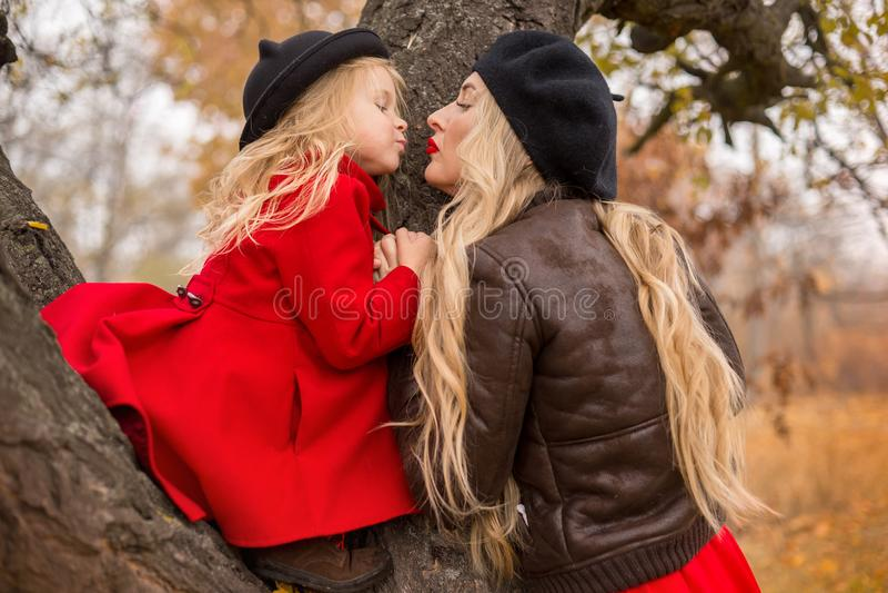 Mädchen in einem roten Mantel kletterte oben einen alten Baum und ihre Mutterunterstützungen lizenzfreies stockbild