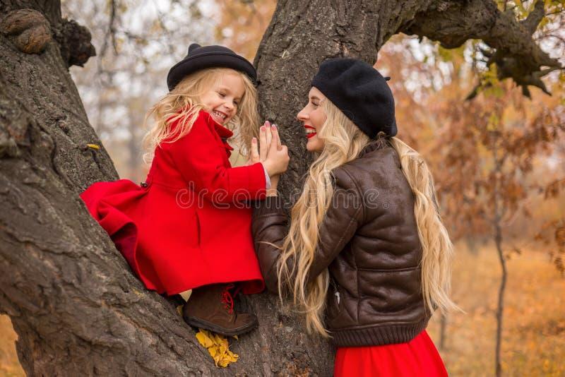 Mädchen in einem roten Mantel kletterte oben einen alten Baum und ihre Mutterunterstützungen lizenzfreie stockbilder