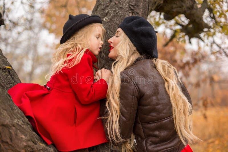 Mädchen in einem roten Mantel kletterte oben einen alten Baum und ihre Mutterunterstützungen stockbild