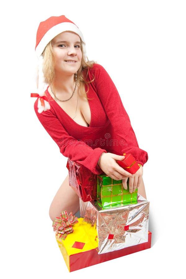 Mädchen in einem Sankt-Hut mit Weihnachtsgeschenken stockfotografie