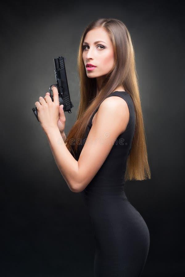 Mädchen in einem schwarzen Kleid, das ein Gewehr hält lizenzfreies stockbild