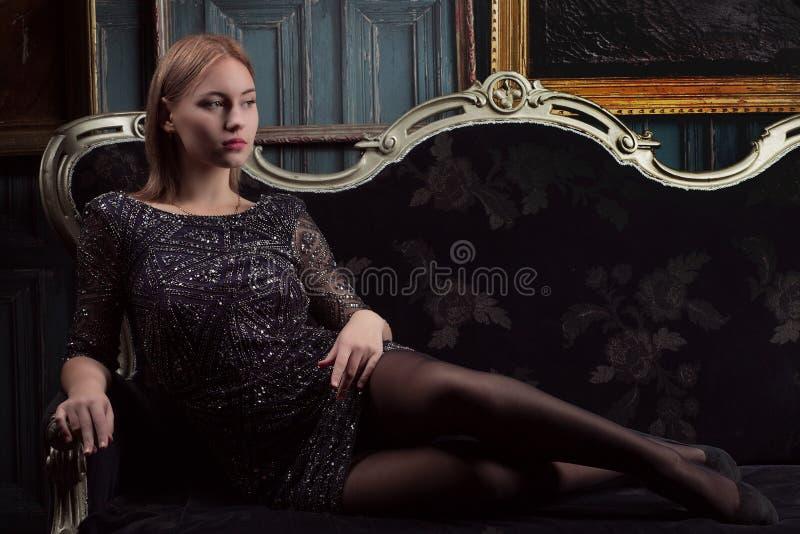 Mädchen in einem schwarzen Kleid im Luxusraum lizenzfreie stockfotografie