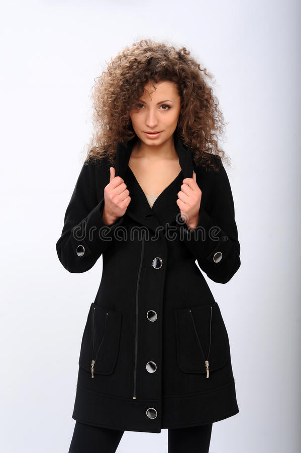 Mädchen in einem schwarzen Mantel lizenzfreie stockbilder