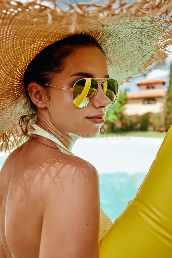 Mädchen in einem Sonnenhut als Nächstes das Pool stockfoto