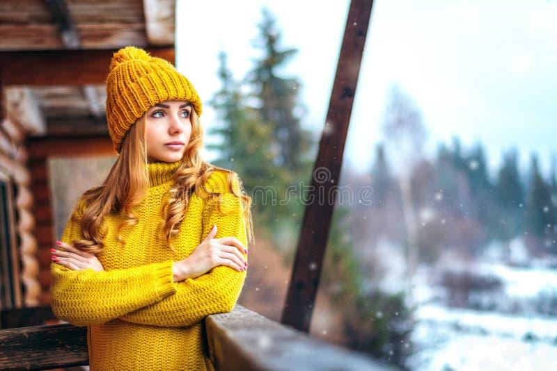 Mädchen in einem Strickpulli, der Schnee betrachtet stockfotografie