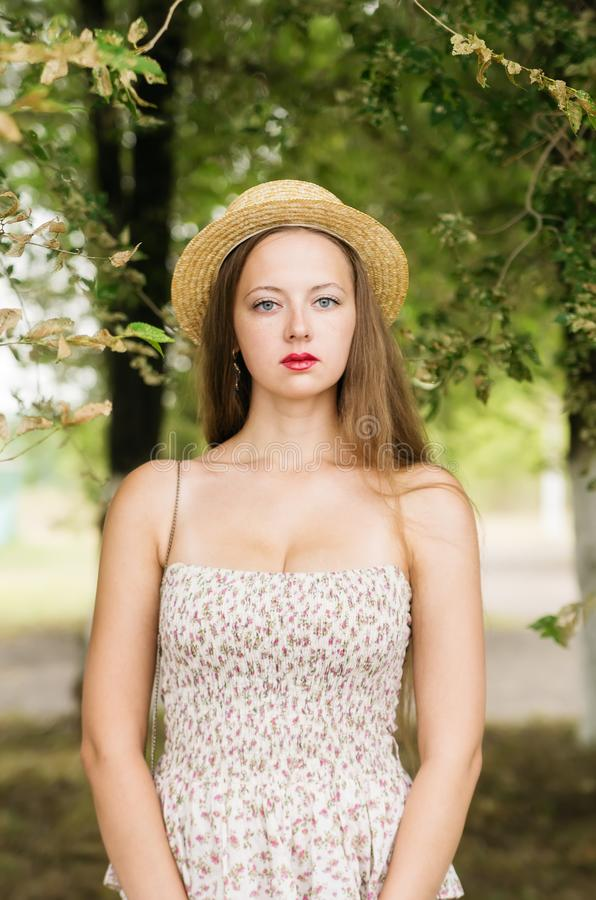 Mädchen in einem Strohhut und Sommer kleiden die Aufstellung in einem Stadtpark stockbild