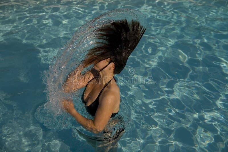 Mädchen in einem Swimmingpool, der nasses Haar wirft lizenzfreie stockfotografie