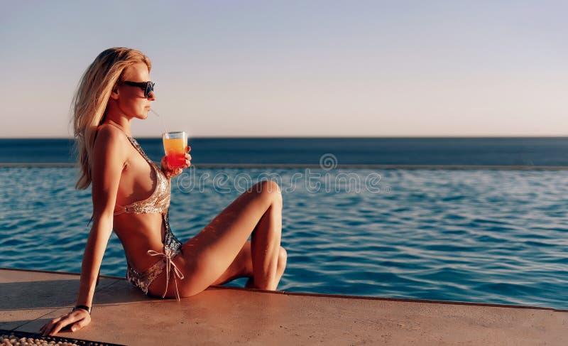 Mädchen in einem teuren Badeanzug mit einem Cocktail in ihren Händen verbringt ihre Ferien nahe dem Pool am Erholungsort lizenzfreie stockfotografie
