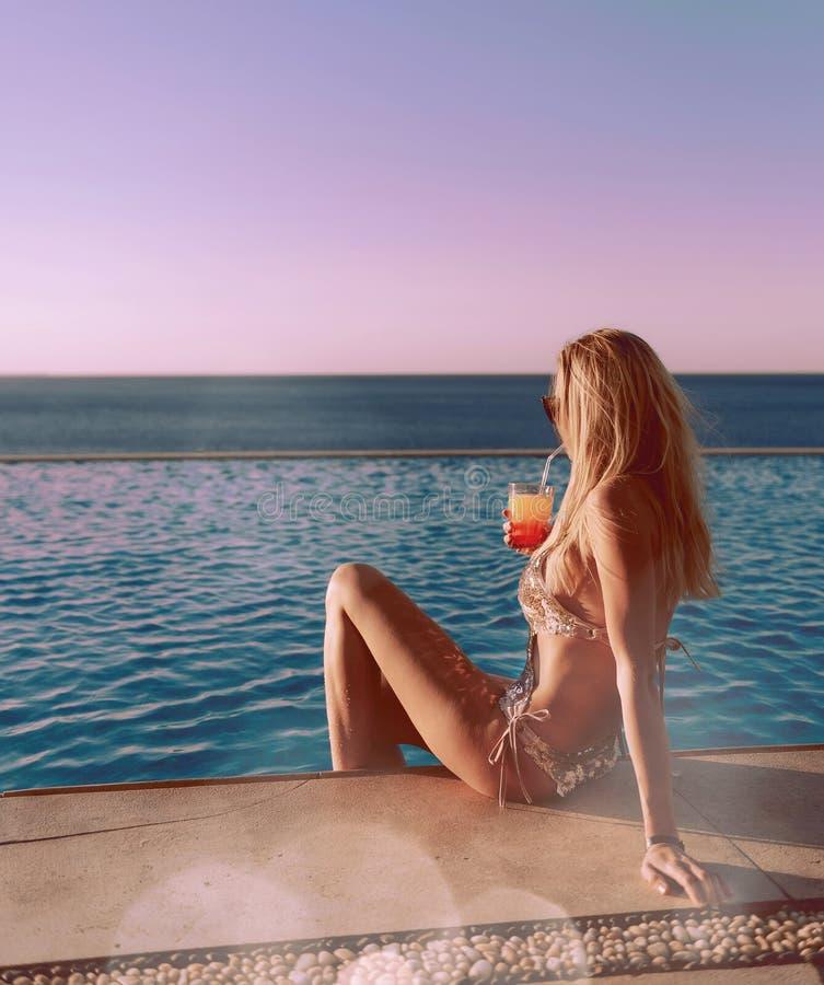 Mädchen in einem teuren goldenen Badeanzug mit einem Cocktail in ihren Händen sitzt am Rand des Pools stockbild