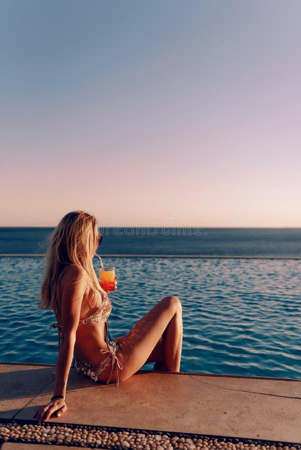 Mädchen in einem teuren goldenen Badeanzug mit einem Cocktail in ihren Händen sitzt am Rand des Pools in den Strahlen der unterge stockfotografie