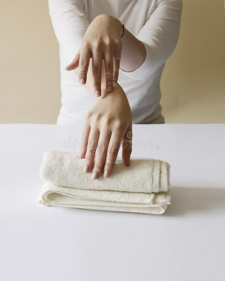 Mädchen in einem weißen Hemd zeigt sie ordentlich und ernährte die Hände, die auf das Sahnetuch gesetzt werden stockfotos