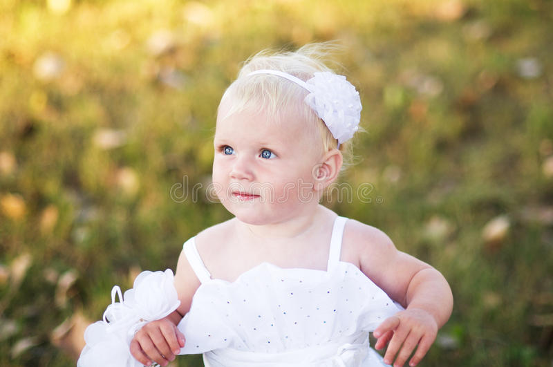 Mädchen in einem weißen Hochzeitskleid auf dem Gras lizenzfreie stockfotografie