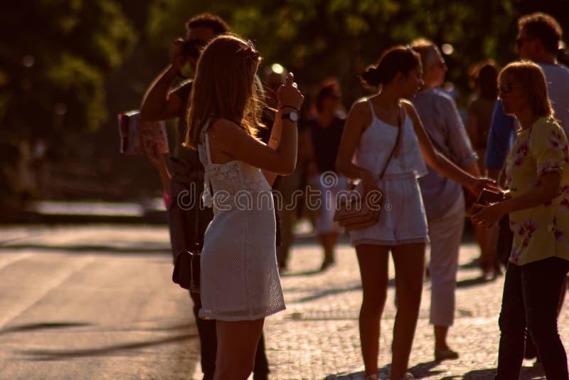 Mädchen in einem weißen Kleid mit Telefon stockbild
