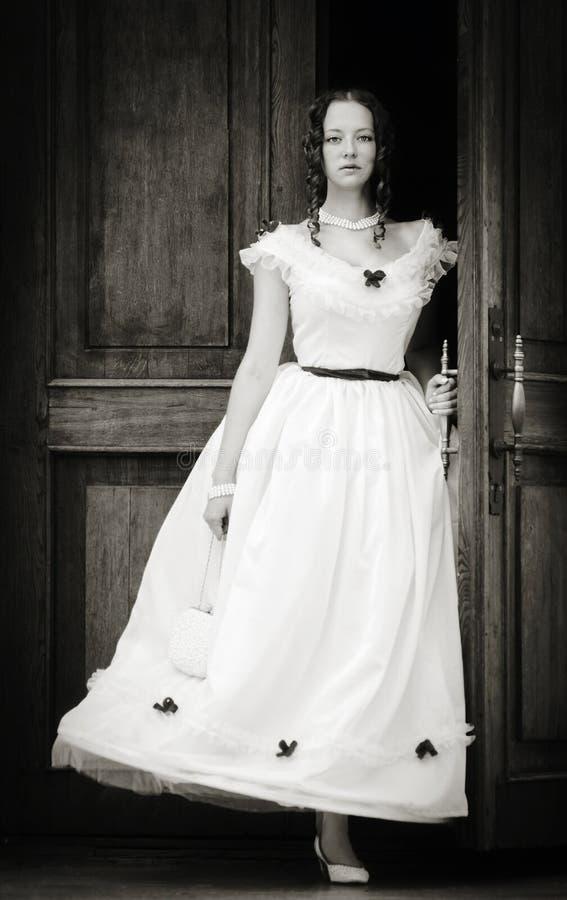 Mädchen in einem Weinlesekleid, das aus Türen herauskommt lizenzfreies stockfoto