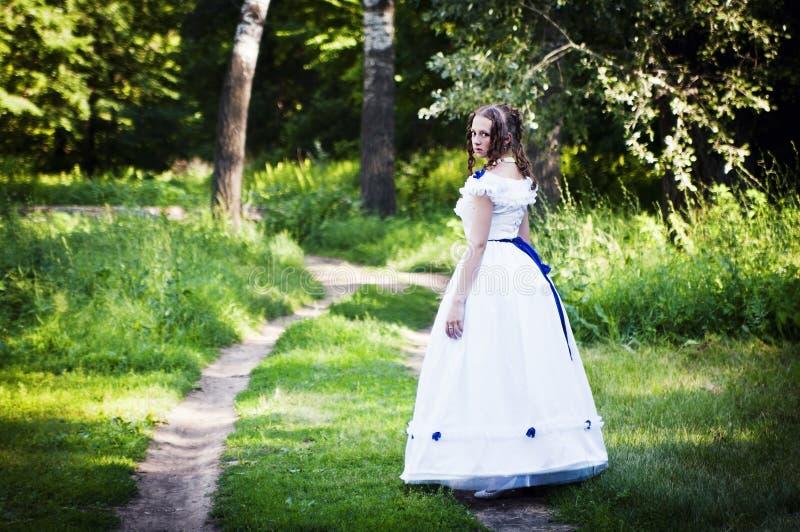 Mädchen in einem Weinlesekleid geht einen Waldweg entlang stockbild