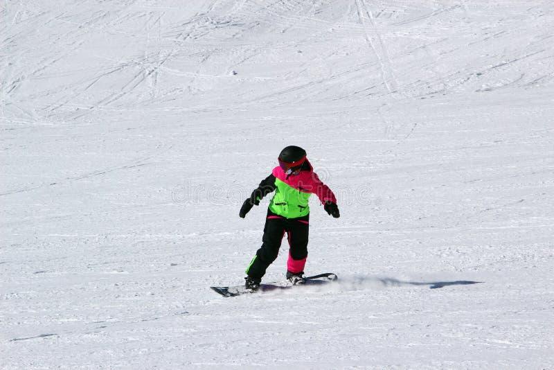 Mädchen in einer bunten Klage ist auf Fahrten eines Snowboard mit Bergen stockfoto
