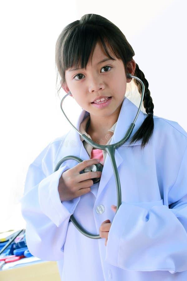 Mädchen in einer Doktoruniform stockbild