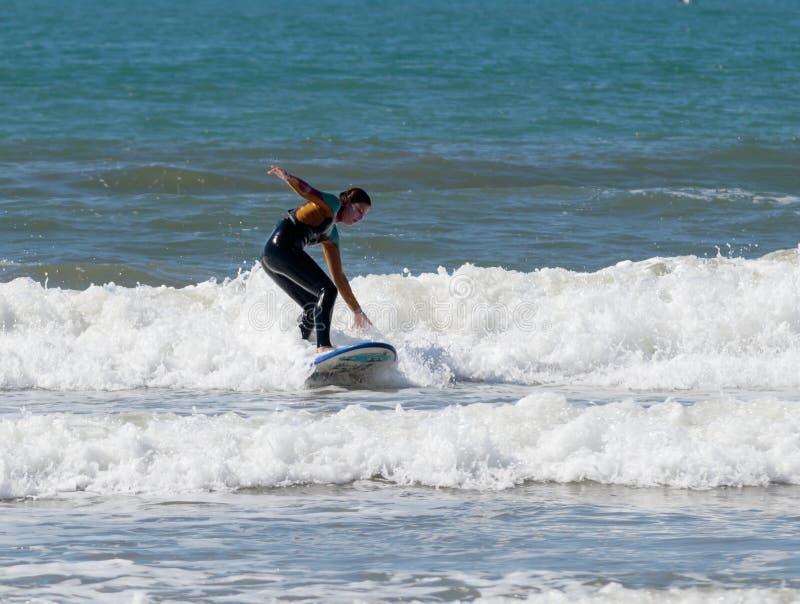 Mädchen in einer Farbwasserdichten Klage trainierend beim Surfen auf das Brett stockfotos