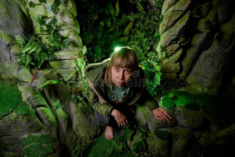 Mädchen in einer grünen Jacke mit dem blonden Haar nahe einem künstlichen Felsen mit einer Grotte Fabelhafte Fotoaufnahme im Stud lizenzfreie stockfotos