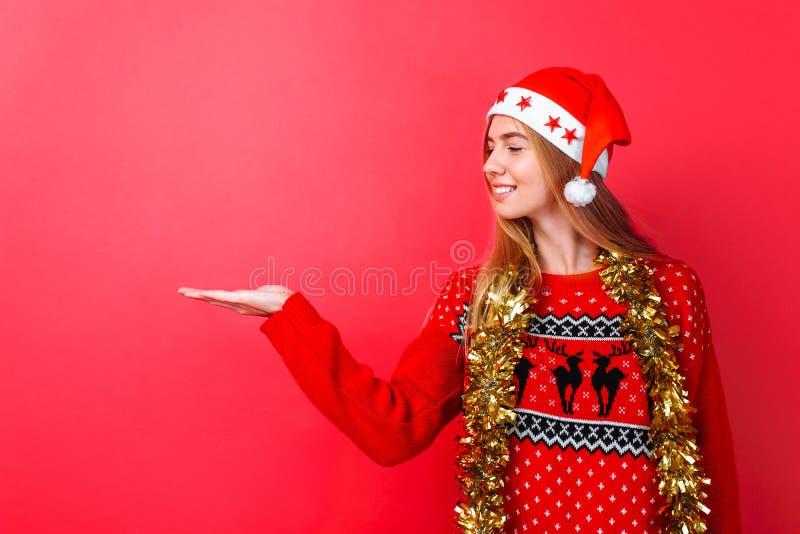 Mädchen in einer roten Strickjacke und in einem Sankt-Hut, mit Lametta um ihren Hals zeigend auf einen leeren Raum auf einem rote lizenzfreie stockfotos