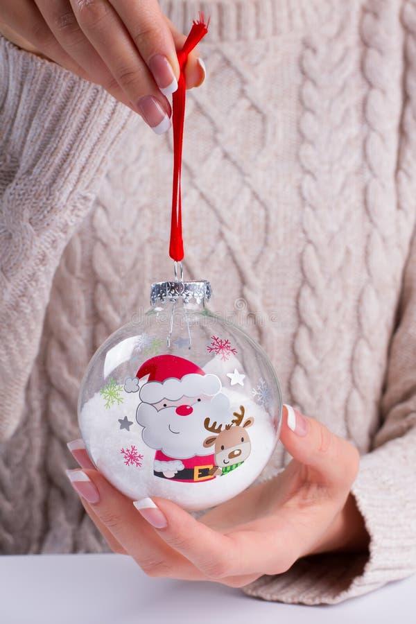 Mädchen in einer schönen gestrickten Strickjacke, die einen Weihnachtsball hält lizenzfreie stockbilder