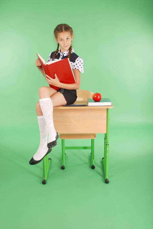 Mädchen in einer Schuluniform, die auf Schreibtisch sitzt und ein Buch liest stockbilder