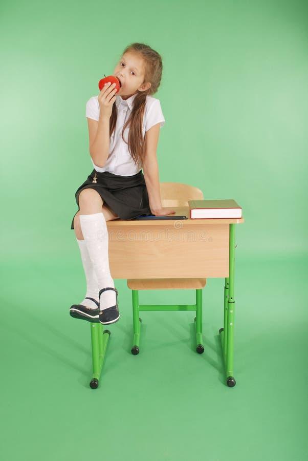 Mädchen in einer Schuluniform, die auf Schreibtisch sitzt und essen Apfel stockfoto