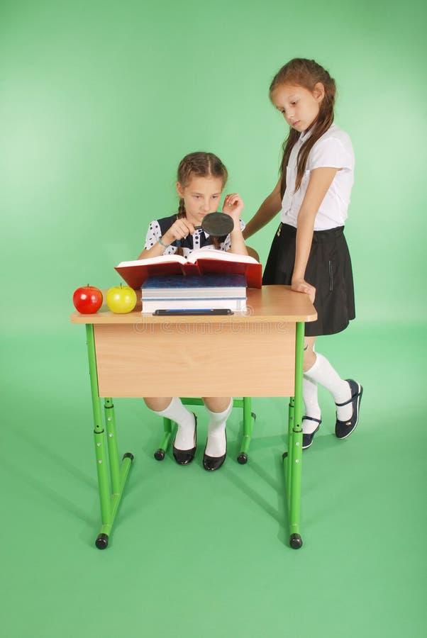 Mädchen in einer Schuluniform, die an einem Schreibtisch mit einer Lupe sitzt stockfotos