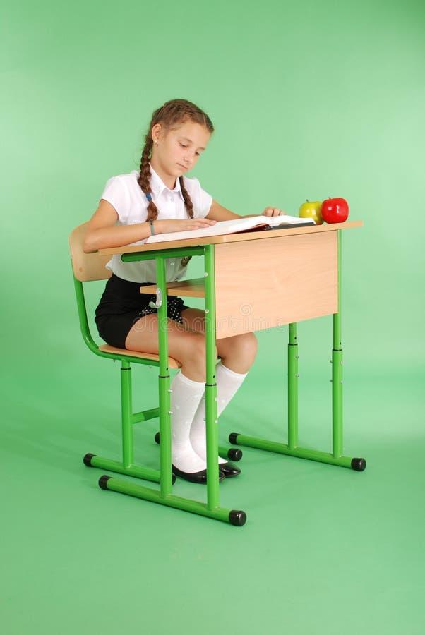 Mädchen in einer Schuluniform, die an einem Schreibtisch sitzt und ein Buch liest lizenzfreies stockfoto