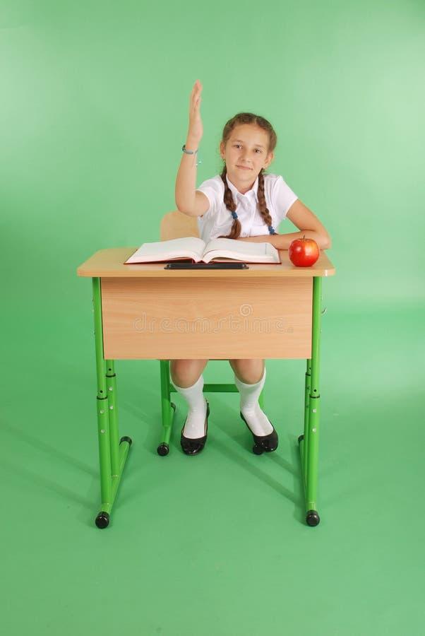 Mädchen in einer Schuluniform, die Hand anhebt, um Frage zu stellen stockbild