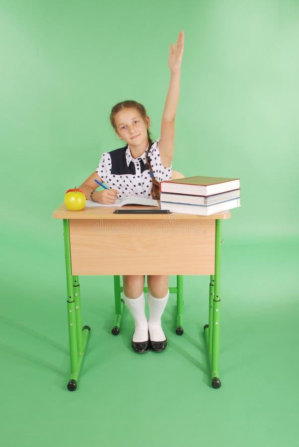 Mädchen in einer Schuluniform, die Hand anhebt, um Frage zu stellen lizenzfreies stockbild
