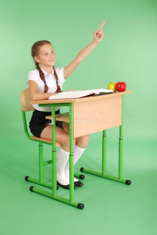 Mädchen in einer Schuluniform, die Hand anhebt, um Frage zu stellen stockfotos
