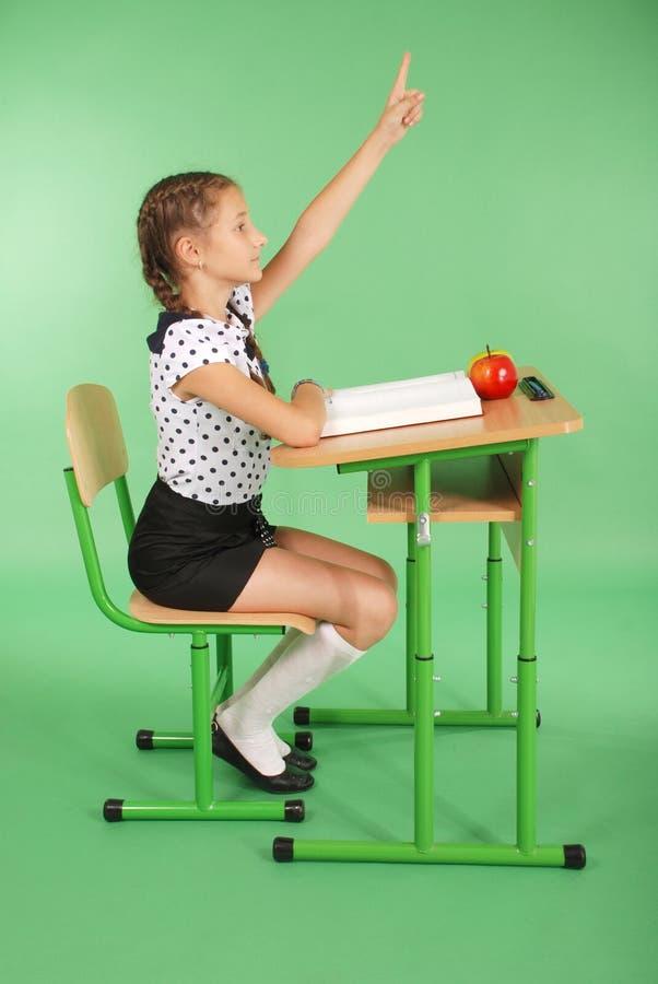 Mädchen in einer Schuluniform, die Hand anhebt, um Frage zu stellen lizenzfreies stockfoto