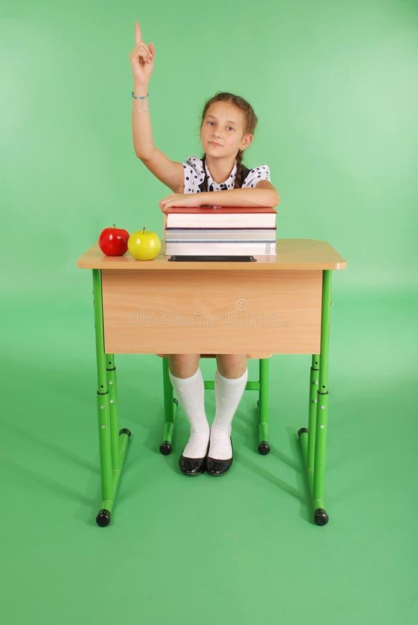 Mädchen in einer Schuluniform, die Hand anhebt, um Frage zu stellen stockbilder