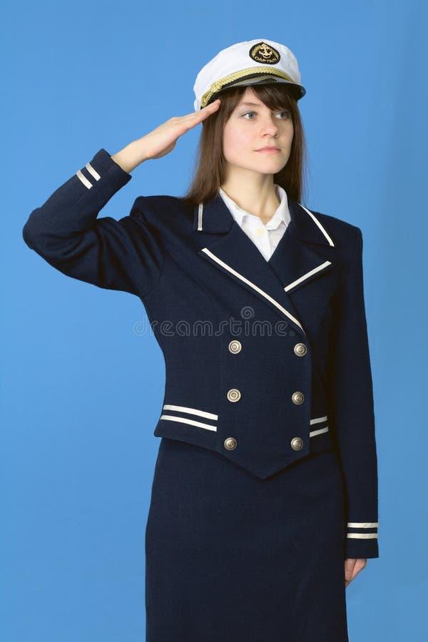 Mädchen in einer Seeuniform begrüßt auf Blau lizenzfreie stockbilder