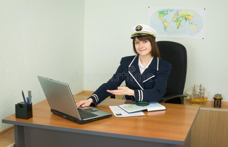 Mädchen in einer Seeuniform am Tisch mit Laptop lizenzfreie stockbilder