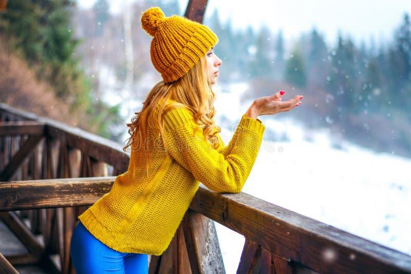 Mädchen in einer Strickjacke und in einem Hut fängt den Schnee lizenzfreie stockbilder