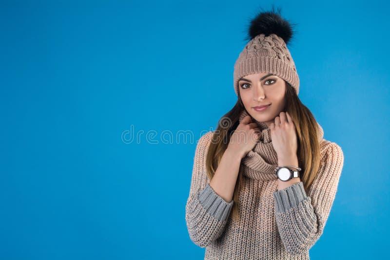 Mädchen in einer warmen Strickjacke, in einem Schal und in einem Hut auf einem blauen Hintergrund lizenzfreies stockbild